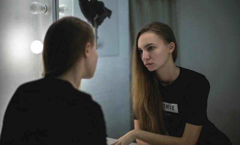 鏡で自分の見た目を確認する女性